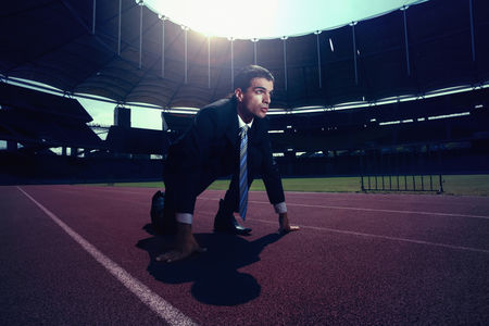 业务 : Businessman crouching on running track