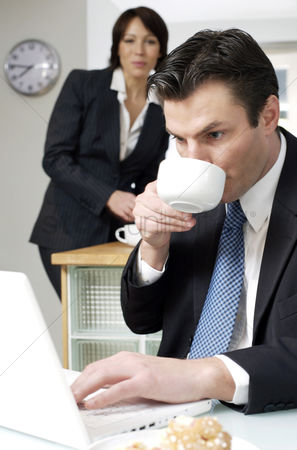 技术 : Businessman drinking coffee while using laptop with his wife in the background