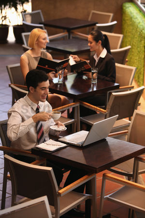 技术 : Businessman drinking coffee while using laptop