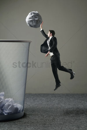 垃圾 : Businessman dunking a giant sized crumpled paper into a big dustbin