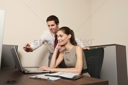 技术 : Businessman explaining something to businesswoman using laptop