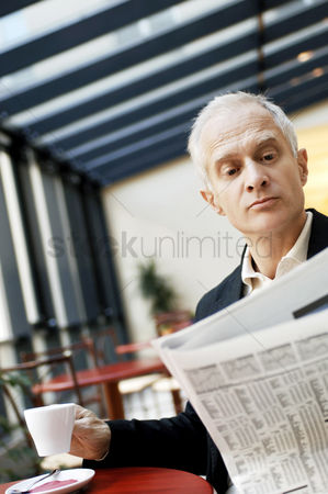 食物 : Businessman holding a cup of coffee while reading newspaper in the cafe