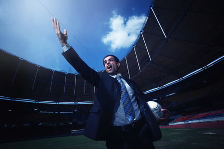 体育 : Businessman holding soccer ball and raising his hand