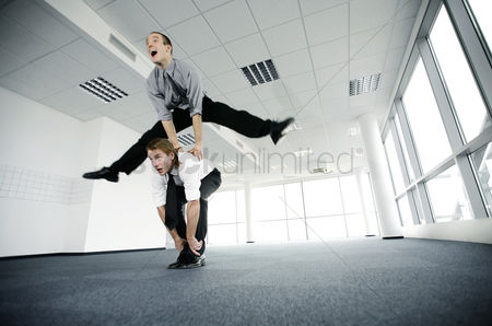 环境 : Businessman jumping over his colleague