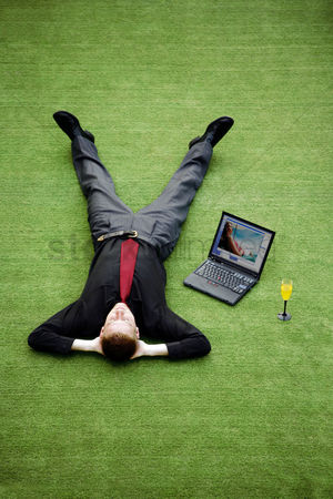 饮料 : Businessman resting on the field with his laptop by the side