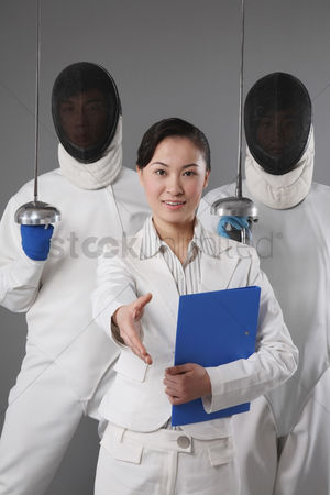 体育 : Businesswoman extending her hand for a handshake with two men in the background