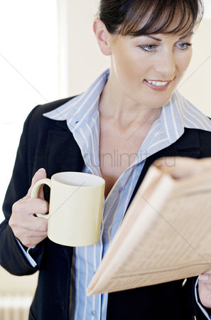 饮料 : Businesswoman holding a cup while reading newspaper