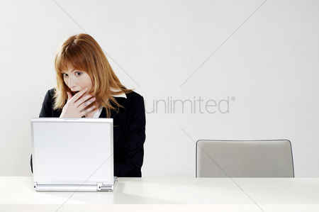 流动性 : Businesswoman in shock while using laptop