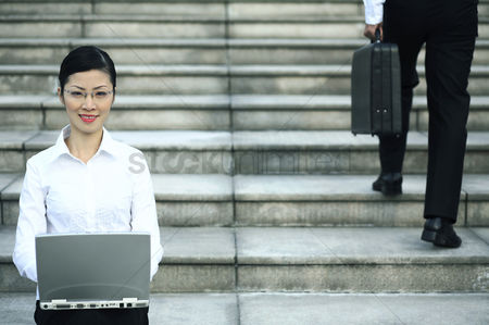 流动性 : Businesswoman sitting at the staircase using laptop