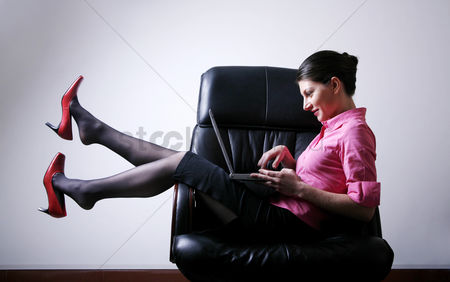 技术 : Businesswoman sitting on the chair playing with laptop
