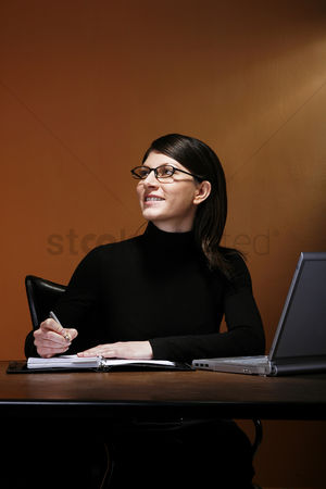 技术 : Businesswoman smiling while writing her organizer