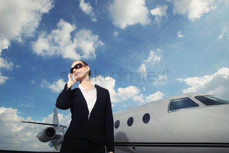 技术 : Businesswoman talking on the phone with private jet in the background