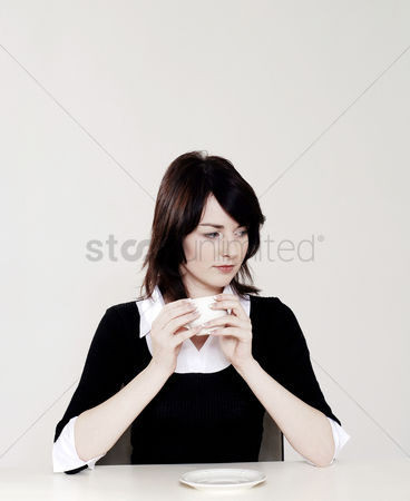 饮料 : Businesswoman thinking while holding a cup of coffee