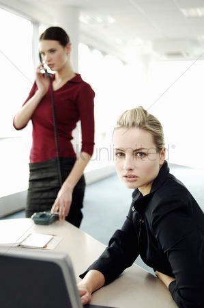 只有成人 : Businesswoman using laptop while her colleague talking on the phone