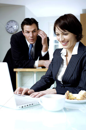 食物 : Businesswoman using laptop with her husband talking on the phone in the background