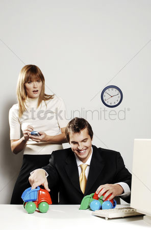 流动性 : Businesswoman using palmtop while her colleague is playing with toy cars
