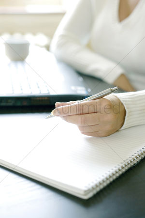 她 : Businesswoman writing on a book while using laptop