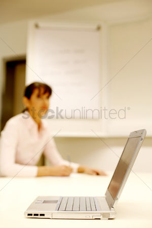技术 : Businesswoman writing on the background with the focus on a laptop