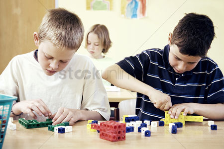 学校 : Children assembling plastic blocks in the classroom