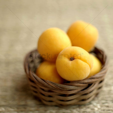 食物 : Close up of some apricots in a woven container