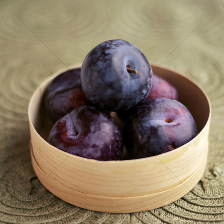 食物 : Close up of some plums in a container