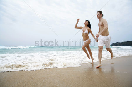 她 : Couple holding hands while running on the beach