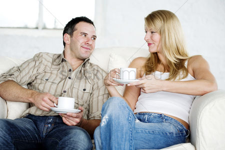 饮料 : Couple resting on couch enjoying coffee
