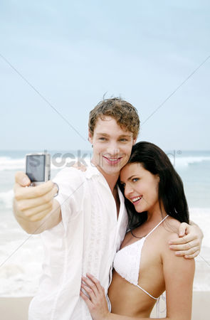 只有成人 : Couple taking picture on the beach