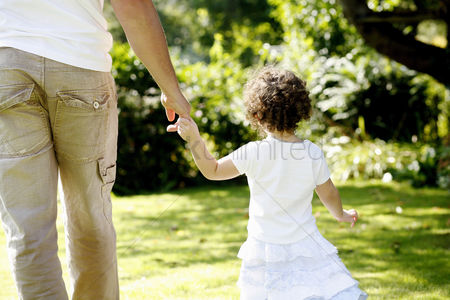 草 : Father and daughter holding hands while walking in the park