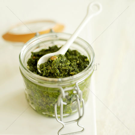 食物 : Fresh italian pesto in a glass jar with a white ceramic spoon