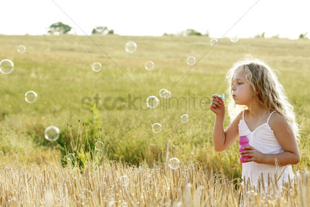 草 : Girl blowing bubbles in the field