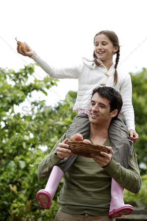 食物 : Girl sitting on man s shoulders with man holding a basket of pears
