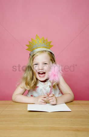 庆典 : Girl with crown smiling while holding a pencil