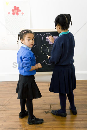 学校 : Girls colouring a drawing on chalkboard