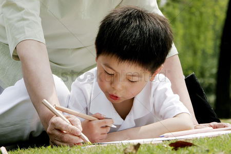 环境 : Grandmother and grandson painting picture in the park
