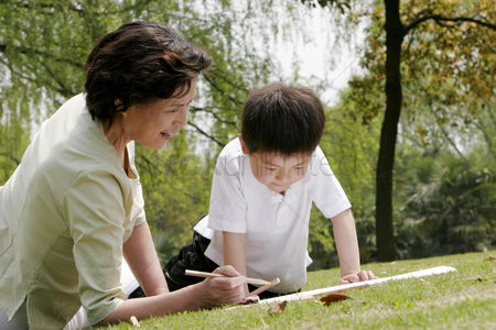 她 : Grandmother and grandson painting picture in the park