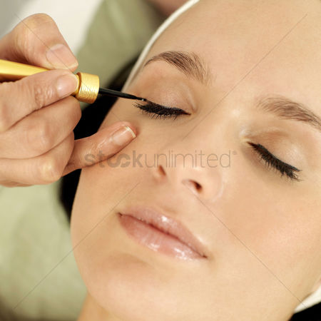 美女时尚 : Hand applying liquid eyeliner on woman s eyelid