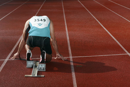 体育 : Male athlete crouching on starting line