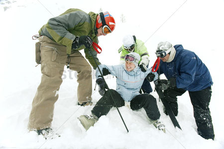 体育 : Male skiers helping female skier
