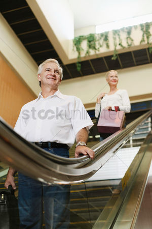 购物 : Man and woman on escalator in airport