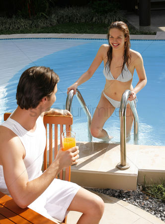 只有成人 : Man enjoying drink by the pool side with his girlfriend climbing out from the pool