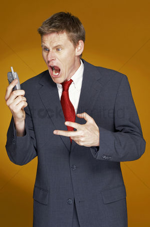 流动性 : Man in business suit shouting angrily on the hand phone