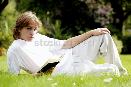 草 : Man lying on the grass holding a book
