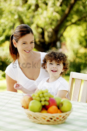 她 : Mother and daughter sitting at the picnic table