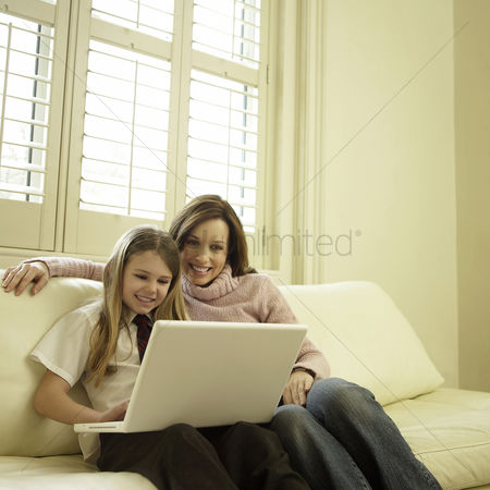 技术 : Mother and daughter sitting on the couch using laptop