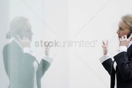技术 : Reflection of a business lady using cell phone