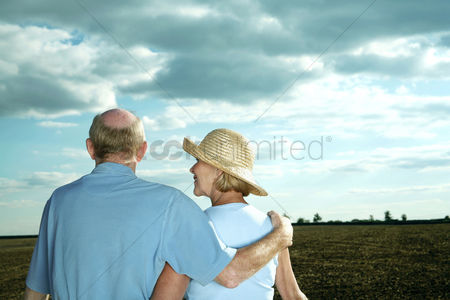 她 : Senior couple enjoying beautiful field scenery