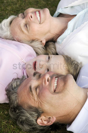 草 : Senior man and woman with a girl lying down on the grass