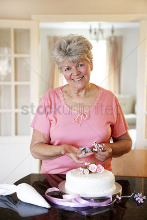 只有成人 : Senior woman decorating cake