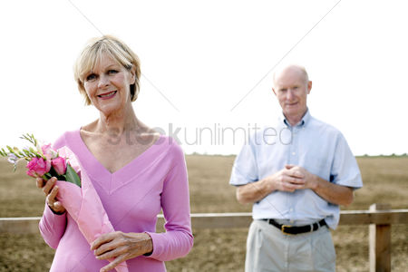 只有成人 : Senior woman holding a bouquet of flowers with her husband standing behind her